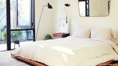 wood platform bed, white linen bedding, and Serge Mouille floor lamp // bedrooms