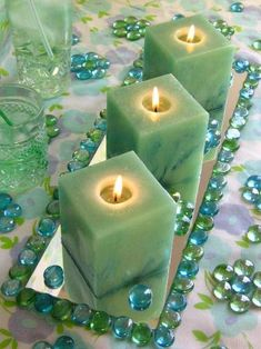 An ornate centerpiece using a rectangular mirror as a  base surrounded with green and blue stones with three square candles all in the same position.