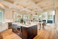 Large kitchen island with sink, white marble countertops, Thermador microwave, coffered ceilings with brass light fixtures.