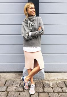 Neck-tied knit over a sweater and front-slit skirt with sneakers.