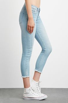 A pair of low-rise ankle jeans with a skinny fit, frayed hem, five-pocket construction, and a zip fly.