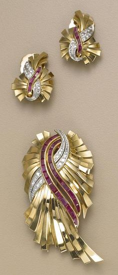 A retro diamond, ruby and eighteen karat gold brooch and pair of earrings, circa 1940.
