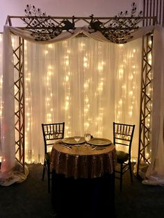 Lighted curtain on gold truss pergola with sweetheart table/Over the Moon Events & Decor – beyond ordinary to extraordinary