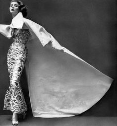 1951 Suzy in gorgeous evening ensemble of gilt embroidered silk sheath worn with a voluminous white faille coat tied in a large bow in front, by Balenciaga