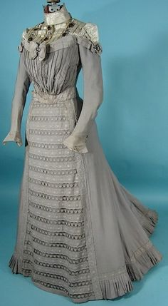 Pale dove grey Victorian day dress (1900)  Exquisite workmanship and lavish detailing, yet this dress doesn't overwhelm.  Flat skirt front falls towards the back and fans into a short train.  Horizontal stripes of embroidered cotton and lace make up the front of the gown.  Long sleeves with tulip cuffs.   Bows on the bosom & shoulders.  More bows down the back.