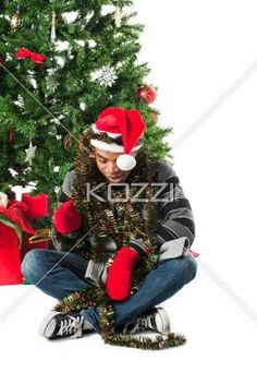 african american man with christmas decorations. - African american man with christmas decorations sitting besides christmas tree. Model: Eddie Reid