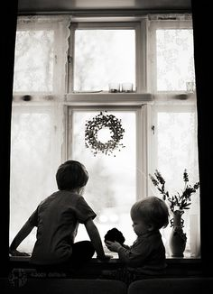 Two little boys looking out the window.