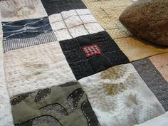 quilt with rock by jude hill. notice pieces of worn fabric