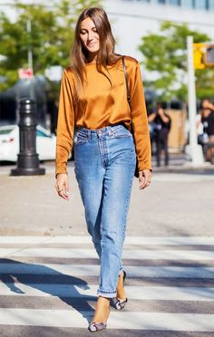 Giorgia Tordini wears a silk top, high-waisted jeans, and pointed-toe python heels