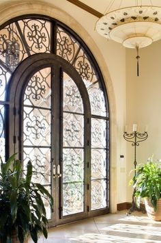 Aren't these iron  glass double doors with an arched surround just lovely! Looks like they are surrounded with traventine or marble. I even love the candelabra  the hanging light fixture.