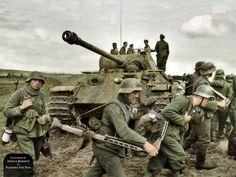 Panzergrenadiers of 131. Infanterie-Division trudge through churned up fields of mud past Panzerbefehlswagen (Command Tank) 'R 02' of 5th SS Panzergrenadier Division 'Wiking'. Atop the tank is SS-Obersturmbannführer Johannes Mühlenkamp, Kommandeur , Kovel, Ukraine. 6th April 1944.