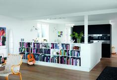 Hvordan forener man drømmen om en stor væg-til-væg reol og biblioteksstemning med ønsket om en åben planløsning og ganske få vægge? JKE Design løste det med en halvhøj reol, der både skaber stemning i stuen og skærmer køkkenet af.