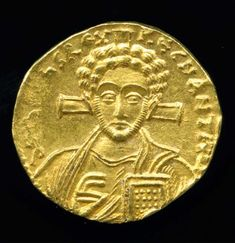 Gold solidus showing a bust of Jesus with a cross behind his head and holding a…