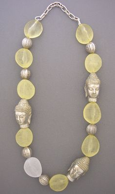 Three white brass Buddha head beads from Indonesia, six carved silver beads, and some unusually shaped and lightweight yellow and white resin beads  comprise this necklace. No clasp, since this one is made to fit over your head.