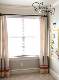 Use a drop cloth from Lowe's ($6.99 from Harbor Freight) and paint for curtains on the cheap... and cute.