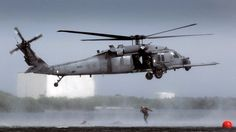 HH-60 Pave Hawk hover as pararescue jumpers enter the water.