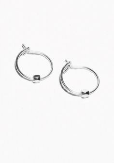 Crafted from brass, these delicate hoop earrings feature a tiny faceted bead.