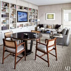 A Milwaukee family room features vintage Edward Wormley for Dunbar armchairs and built-in bookcases that house a television.