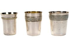 """A set of three silverplate tumblers. Largest is monogrammed with the letter """"L"""" and has no maker's mark; medium size has a """"C"""" monogram, a decorative band around the top, and an illegible mark on the underside; smallest has a raised band around the top and an illegible mark on the underside. Dimensions: large, 2.75""""Dia x 3""""H; medium, 2.5""""Dia x 3""""H; small, 2.25""""Dia x 3""""H."""