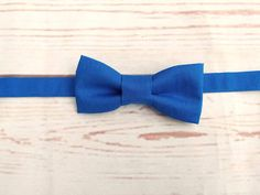 **Made to order**   Boys classic plain royal blue bow tie. This colour works very well for many suit or shirt colours  100% quality cotton fabric  Bow ties are designed to be worn with collar stand shirts. If you would like a clip on style instead, please message me   --------------------------------------------------------------------  Sizes and measurements  Age 6 to 18 months, finished pre tied bow for size 6 to 18 months is 1 7/8 x 3 7/8 inches. The length of the band is just un...