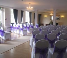 White chair covers with purple bows for wedding ceremony.