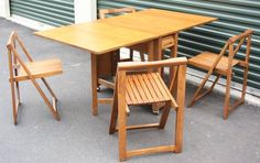 Vintage Teak Foldable Table and 4 Folding Chairs. Chairs fit inside table and a door slides up and down to conceal them. $350