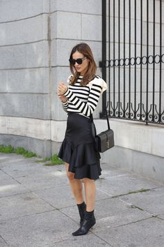 ruffle top looks - Lady Addict. Black and white streiped ruffle top+black ruffle asymmetric satin skirt+black kitten heeled ankle boots+black shoulder bag+black coat with golden buttons+black sunglasses. Winter To Spring Transition Dressy Casual Outfit 2017