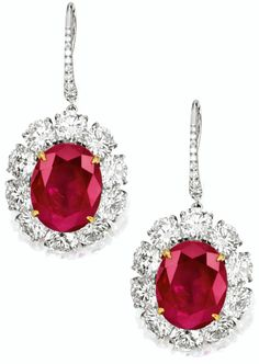 PAIR OF RUBY AND DIAMOND PENDENT EARRINGS    Each suspending on an oval ruby weighing 12.17 and 10.46 carats respectively, surrounded by brilliant-cut diamonds extending to the hook surmount, the diamonds altogether weighing approximately 11.05 carats, mounted in platinum and 18 karat yellow gold. Sotheby's.