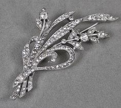 It is marked TRIFARI and DES PAT NO 129319. The patent number was issued to Alfred Spaney, a Trifari designer, in 1941.The pin is a floral spray motif, in rhodium plated metal. It is decorated with pave set crystal rhinestones. The pin measures 3 1/2 inches long. In very good condition, however the pin catch has been replaced by a previous owner. It is in fine working order. A sparkling beauty!!