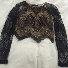 Black and nude lace cropped top This is a black lace cropped top with nude fabric underneath. It is long sleeved. Size medium. It has never been worn! ANGL Tops Crop Tops