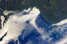 Gravity Waves and Sunglint, Lake Superior | NASA From the the International Space Station, astronauts observe atmospheric and surface phenomena in ways that are impossible to view from ground. Two such phenomena—gravity waves and sunglint—are illustrated in this photograph of northeastern Lake Superior. Offshore several distinct sets of parallel cloud bands are visible. Gravity waves are produced when moisture-laden air encounters imbalances in air density, when cool air flows over warmer…