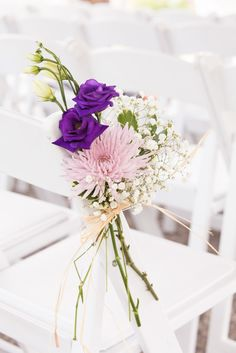 A pretty bouquet in pink, purple and white livens up the ceremony chairs. photo: www.eyecontact.ca