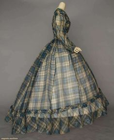 """leno weave silk in blue & white plaid w/ touches of green & yellow, vertically ruched F & B bodice, silk piped bishop sleeves, 7 domed blue thread buttons, inset W band, voluminous cartridge pleated skirt, white lace & ruched self fabric trims, white silk under bodice, small sewn in tag """"Endicott"""", B 33"""", W 22"""", L 59""""-65"""""""