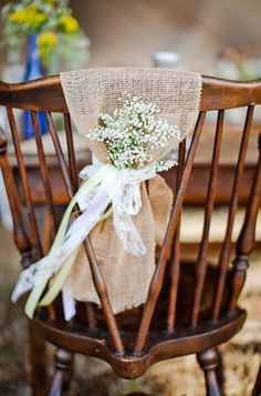Wedding Chair Swag - A wooden chair is decorated with a strip of burlap and tiny flowers wrapped up to create the most devine wedding chair decor. #chair #decor #chaise