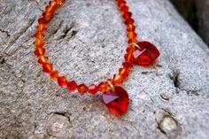 Pulsera con cristales rojo tornasol y corazones rojos. Broche de plata dorada.