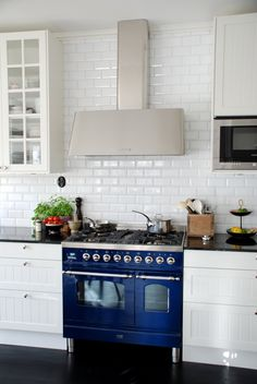 A beautiful blue range with white display cabinets, subway tile, hood, and dark floor.