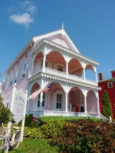 Sweetest pale pink Victorian home!!!!!!lots of ginger breading on the two story porches!