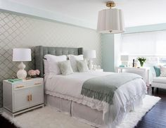 Green and gray bedroom features an accent wall clad in green and gold scallops wallpaper lined with a gray velvet wingback headboard on bed dressed in white scalloped bedding, green Moroccan tiles pillows in Windsor Smith Riad Fabric and a gray fringed throw blanket.