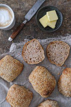 Sprøde surdejsboller vendt i sesamfrø i både top og bund. Sesamfrøene giver bollerne en mild, sødlig og nøddeagtig smag – en aroma, som særligt udvikler sig når frøene ristes, når bollerne bages i ovnen. Bread, Kitchens, Breads, Bakeries