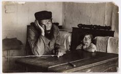 Dlugosiodlo. A man sits for an informal portrait with a child in his home. 'Hirsh Neyman. An unfortunate man.'