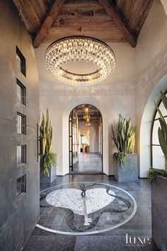 A hand-forged steel door fabricated by Metalworks leads to the entry tile mosaic by Venetian Tile & Stone Gallery. An Arctic Pear chandelier by Ochre shimmers above; the custom concrete planters are by Hart Concrete Design. Entry Chandelier, Industrial Chandelier, Interior And Exterior, Interior Design, Entry Hallway, Entry Tile, Concrete Design, Steel Doors, Steel Windows