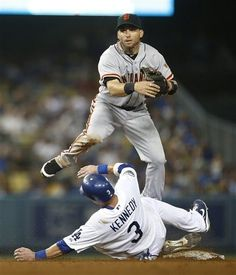 Giants second baseman Marco Scutaro, top, throws to first base after forcing out Los Angeles Dodgers' Adam Kennedy in the fourth inning of a baseball game in Los Angeles, Tuesday, Aug. 21, 2012. Matt Kemp was out at first.