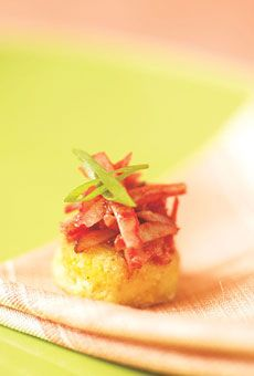 mini cheddar corn cakes topped with glossy pink slivers of candied pork and snips of scallion.