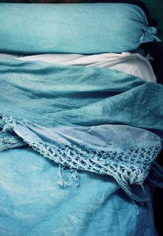 Throw some linen fabric in the wash with blue dye, and add long fringe trim to the top and bottom and have the summery linen bed-cover you've been after without the $400 price tag.
