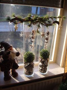 Hoge vazen met een tak van groen met versiering..even onthouden voor de kerst..