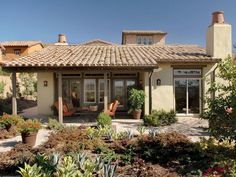 The rear loggia creates a comfortable, shady sitting area under the extended roof. The home's stucco exterior is enhanced with colorful, sun-loving plants just beyond the patio space for an authentic Southwest-style look.