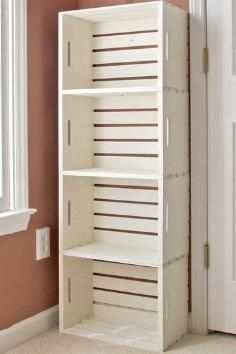 Buy four unfinished wooden crates from Michael's ($12.99 each), spray painting them white, tacking them together and then bolting them to the wall.