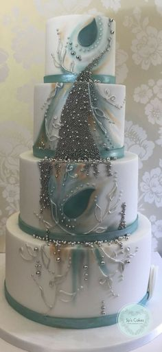 This was one of the most challenging wedding cakes for me but I absolutely love it! The bride gave me free rein to decorate the cake. The theme was wintery wedding and her favourite colour is teal. I went with the idea of ice and evergreen leaves for wintery feel and the warmth of fire during winter. #bespokeweddingcake #luxuryweddingcakes #Hertfordshire