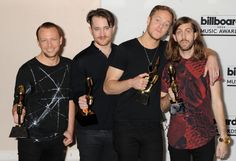 """Ben McKee, and from left, Daniel Platzman, Dan Reynolds, and Wayne Sermon, of the musical group Imagine Dragons, poses in the press room with the award for top rock album for """"Night Visions"""" at the Billboard Music Awards at the MGM Grand Garden Arena 2014"""
