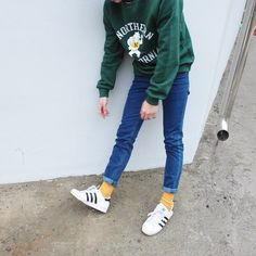 Contrasting green crewneck and yellow socks peeking from under rolled up jeans.